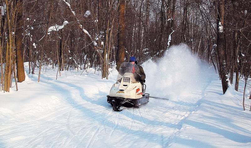 движение на снегоходе по трассе с плотным снегом